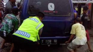 Aiptu Dwi raharjo anggota PolsekKertek saat mengangkat mobil