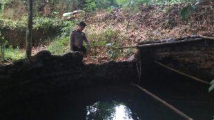 Personil Polsek Sapuran Brigadir Arwianto Nugroho menunjukanlokasi penemuan mayat Laki Laki yang ditemukan mengapung di penampungan bak mandi turut di Dusun Peniron Desa Talunombo Sapuran