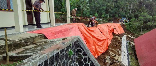 Polsek Sapuran, BPBD Kabupaten Wonosobo, Relawan Kecamatan Kalibawang dan Warga menggelar terpal sisa senderan yang longsor di SMPN 3 Kalibawang