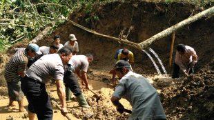 Personil Polsek Sapuran Polres Wonosobo bersama dengan warga mebersihkan material longsor yang menimpa rumah milik Bp. Sugiyono di Dusun Grenjeng Desa Kalikarung Kecamatan Kalibawang